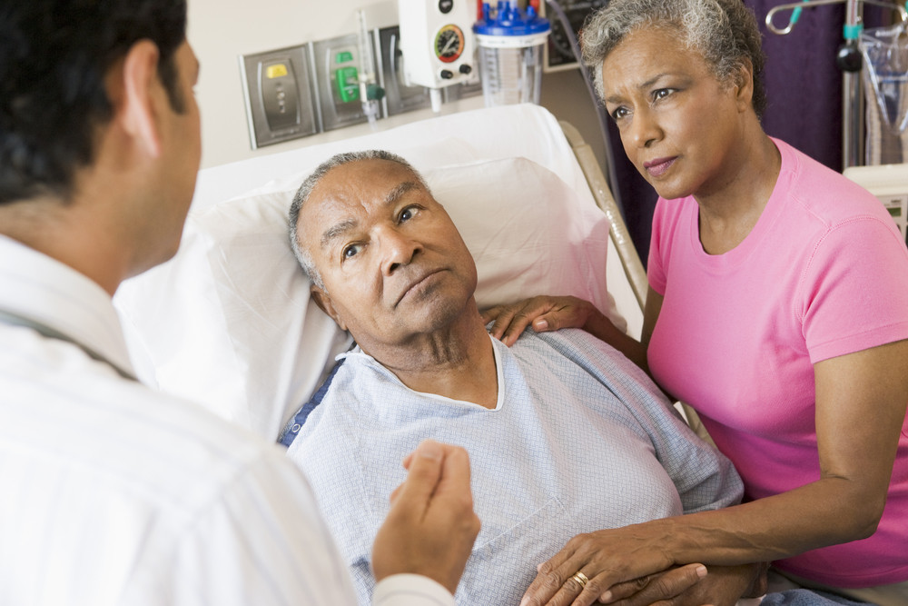 Man unwell in bed looking at doctor